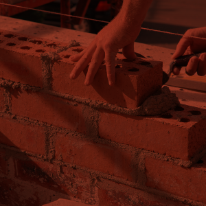 Bricklayer spreading mortar and placing brick
