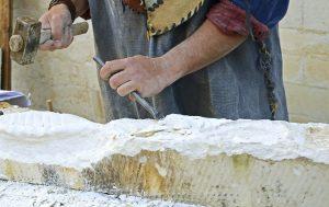 Stonemason chiseling a cube of sandstone
